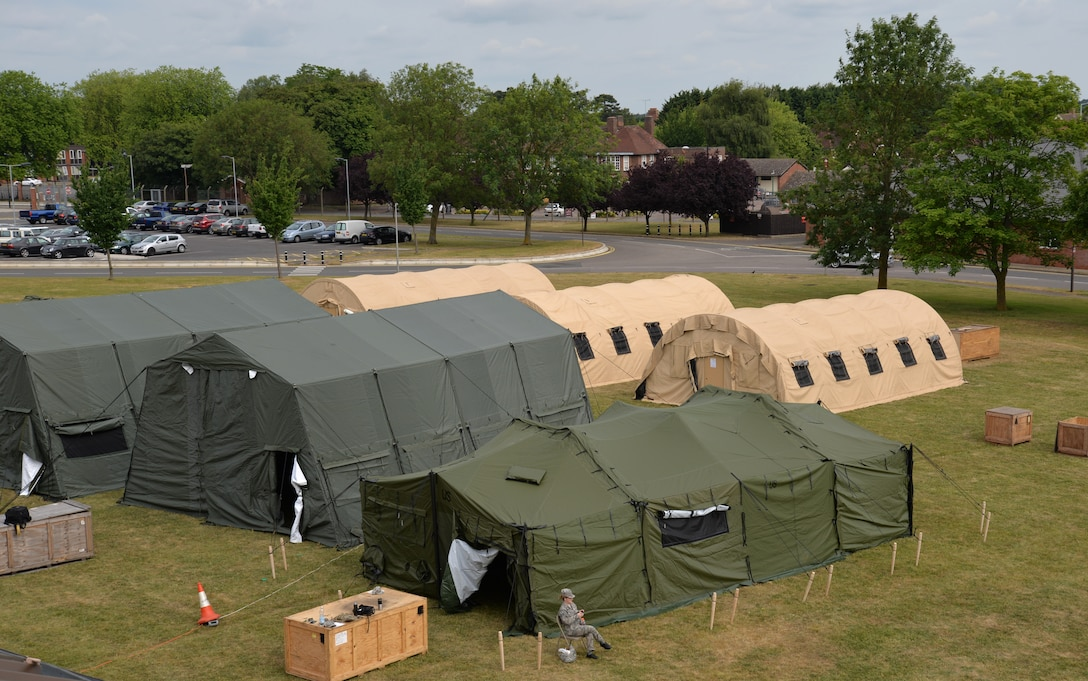 """U.S. Air Force Airmen from the 100th Civil Engineer Squadron Structures shop stand up """"tent city"""" June 25, 2015, during 100th CES bivouac training on RAF Mildenhall, England. The tents facilitated lodging for 76 Airmen and training which included team movement techniques, land navigation, use of night vision goggles and Humvee driving. The structures career field is often called upon to provide sleeping arrangements for service members in expeditionary environments. A six-man team can provide comfortable lodging for over 100 people in one day. (U.S. Air Force photo by Karen Abeyasekere/Released)"""