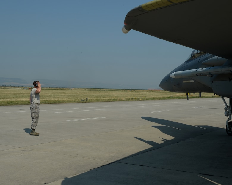 A U.S. Air National Guard crew chief from the 123rd Expeditionary Fighter Squadron salutes the pilot of an U.S. Air Force F-15C Eagle fighter aircraft during a theater security package deployment July 7, 2015, at Campia Turzii, Romania. The aircraft deployed to Romania in support of Operation Atlantic Resolve to bolster air power capabilities while underscoring the U.S. commitment to European security and stability. (U.S. Air Force photo by Senior Airman Dylan Nuckolls/Released)