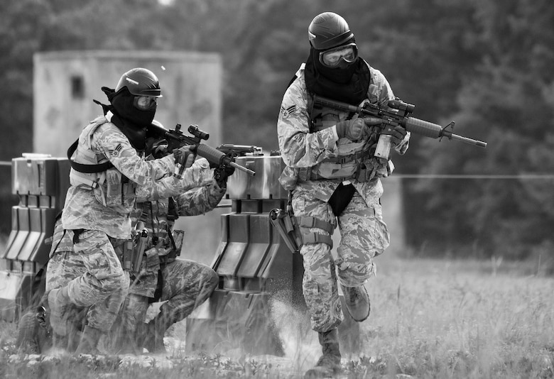 A team of 96th Security Forces Squadron Airmen perform a side-advancing movement during a shoot, move and communicate drill in June at Eglin Air Force Base, Fla.  The mandatory training requirement is in addition to annual weapons qualification training.  The exercise consists of Airmen firing simmunition ammo while advancing toward, away from and to the side of a target.  This is followed by a building sweep and clear drill. Eglin's security forces personnel protect and defend the main base, facilities, gates, Duke Field, 7th SFG compound and land and water ranges.  (U.S. Air Force photo/Tech. Sgt. Sam King)