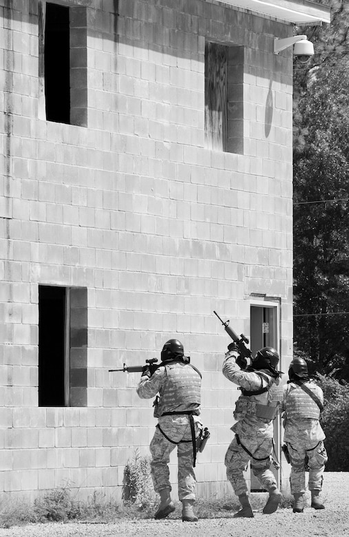 A team of 96th Security Forces Squadron Airmen advance into a building entrance during a shoot, move and communicate drill in June at Eglin Air Force Base, Fla.  The mandatory training requirement is in addition to annual weapons qualification training.  The exercise consists of Airmen firing simmunition ammo while advancing toward, away from and to the side of a target.  This is followed by a building sweep and clear drill.  Eglin's security forces personnel protect and defend the main base, facilities, gates, Duke Field, 7th SFG compound and land and water ranges.  (U.S. Air Force photo/Tech. Sgt. Sam King)
