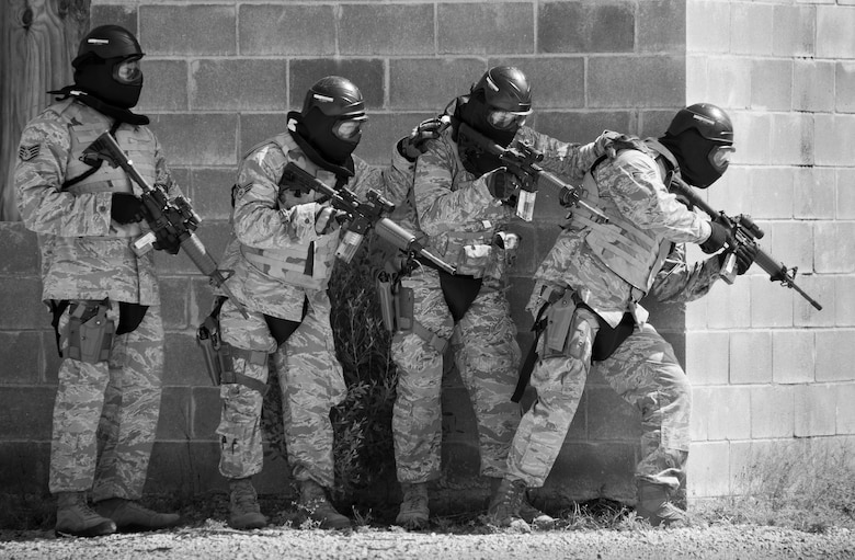 A team of 96th Security Forces Squadron Airmen prepare to enter a building during a shoot, move and communicate drill in June at Eglin Air Force Base, Fla.  The mandatory training requirement is in addition to annual weapons qualification training.  The exercise consists of Airmen firing simmunition ammo while advancing toward, away from and to the side of a target.  This is followed by a building sweep and clear drill.  Eglin's security forces personnel protect and defend the main base, facilities, gates, Duke Field, 7th SFG compound and land and water ranges.  (U.S. Air Force photo/Tech. Sgt. Sam King)