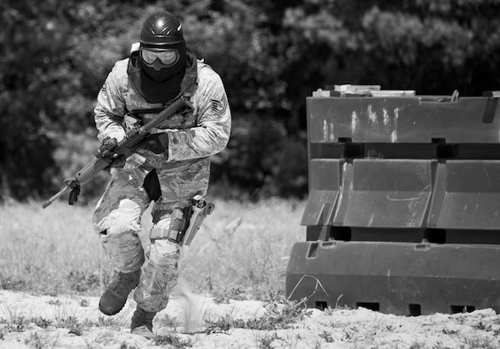 A 96th Security Forces Squadron Airman moves toward a barrier during a shoot, move and communicate drill at Eglin Air Force Base, Fla.  The mandatory training requirement is in addition to annual weapons qualification training.  The exercise consists of Airmen firing simmunition ammo while advancing toward, away from and to the side of a target.  This is followed by a building sweep and clear drill.  Eglin's security forces personnel protect and defend the main base, facilities, gates, Duke Field, 7th SFG compound and land and water ranges.  (U.S. Air Force photo/Tech. Sgt. Sam King)