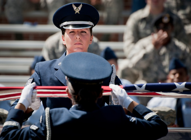 Senior Airman Christen Neel holds the flag during an Honor Guard graduation ceremony at Eglin Air Force Base, Fla. Approximately 12 new Airmen graduated from the 80-plus-hour course. The graduation performance includes flag detail, rifle volley, pall bearers and bugler for friends, family and unit commanders.  The Eglin Honor Guard provides their services to the base, Duke Field and more than 20 area counties making up approximately 20,000 square miles in the Florida and Alabama region.  (U.S. Air Force photo/Tech. Sgt. Sam King)