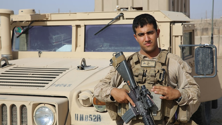 Lance Cpl. Ali J. Mohammed poses for a photo with a Humvee aboard Al Taqaddum Air Base, Iraq, July 4, 2015. Mohammed is originally from Baghdad and is now serving in the U.S. Marine Corps as a supply Marine. He is currently deployed as an Arabic interpreter for Task Force Al Taqaddum.