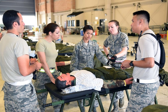 Airmen from the 59th Medical Wing, Joint Base San Antonio-Lackland, Texas, discuss a simulated patient's care during aeromedical evacuation processing in an Ultimate Caduceus 2015 exercise at Naval Air Station Joint Reserve Base New Orleans, La., April 16, 2015. Ultimate Caduceus 2015 consists of approximately 140 military personnel representing active duty, National Guard and Reserve forces from California, Delaware, Illinois, Kansas, Louisiana, Maryland, Mississippi, Texas and Washington, D.C. (U.S. Air National Guard Photo by Master Sgt. Dan Farrell, 159th Fighter Wing Public Affairs Office/Released)
