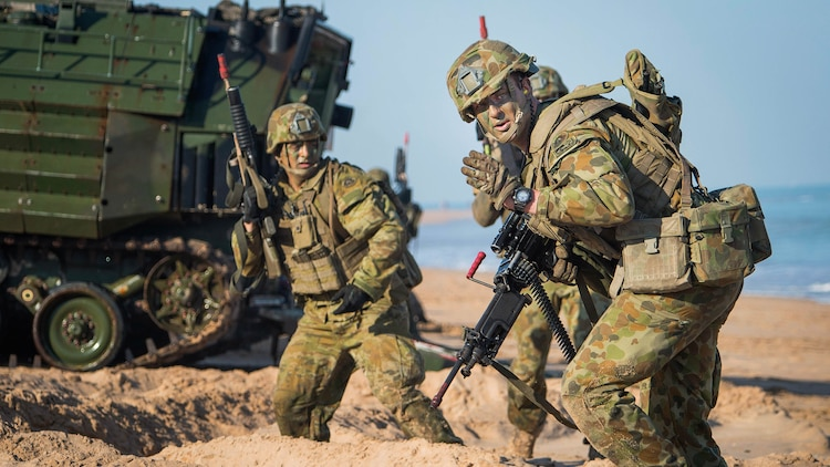 An Australian Army Soldier, assigned to 2nd Battalion, Royal Australian Regiment, motions to move forward during an amphibious assault for Talisman Sabre 2015 at Fog Bay, Australia, July 11, 2015. Talisman Sabre is a biennial exercise that provides an invaluable opportunity for nearly 30,000 U.S. and Australian defense forces to conduct operations in a combined, joint and interagency environment that will increase both countries' ability to plan and execute a full range of operations from combat missions to humanitarian assistance efforts.