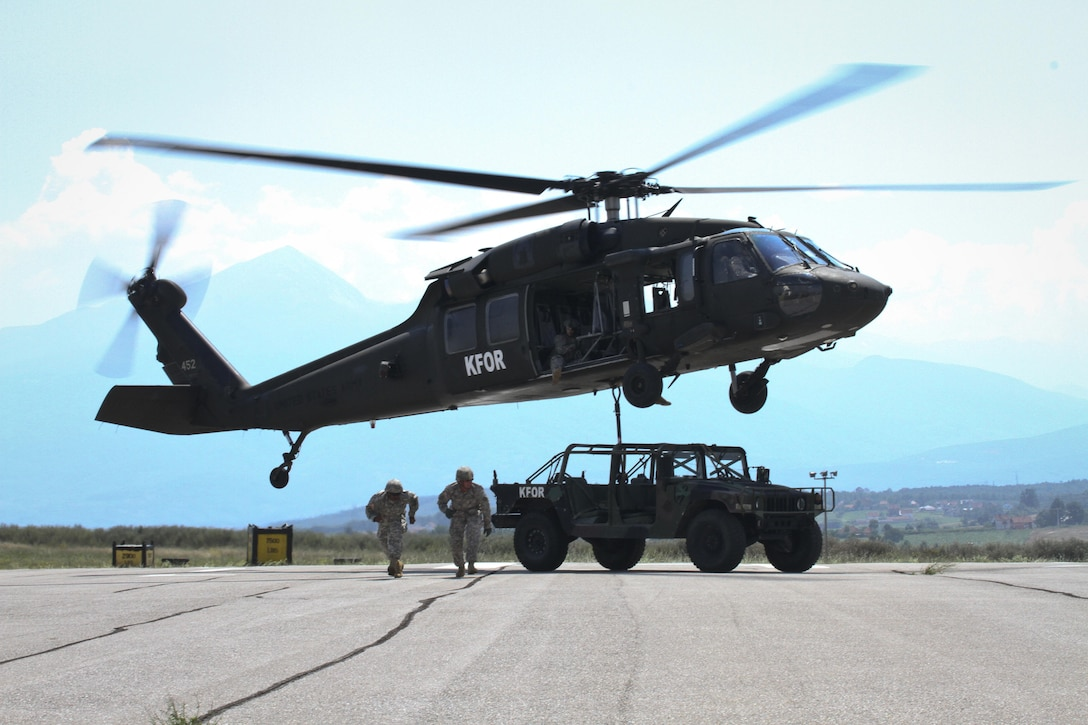 Soldiers assigned to Multinational Battle Group-East clear a helicopter pad after sling loading a HUMVEE on a UH-60 Black Hawk helicopter during a July 6, 2015, familiarization training event at Camp Bondsteel, Kosovo. The training was conducted to help familiarize incoming Multinational Battle Group-East Soldiers with sling load operations and procedures. (U.S. Army photo by Staff Sgt. Jeffrey Bennett, Multinational Battle Group-East)