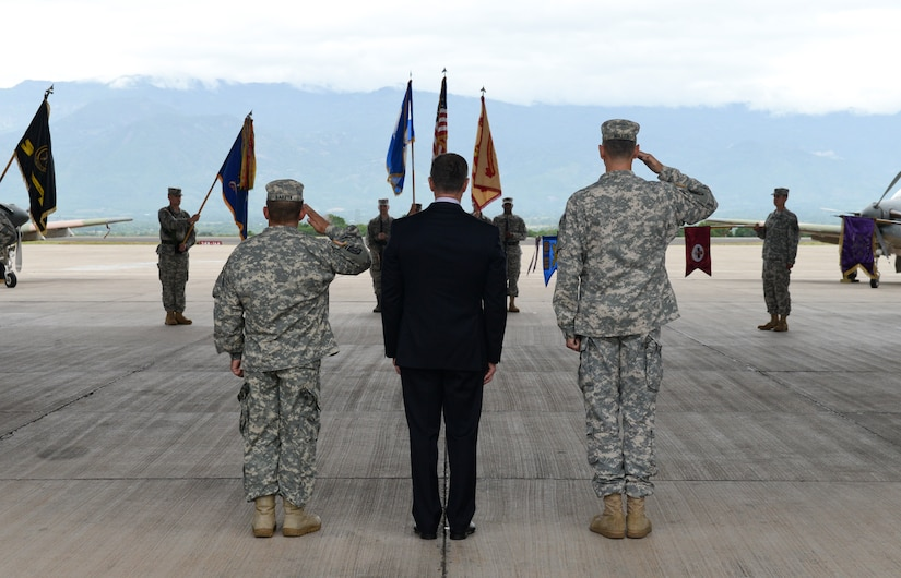 From left to right, Col. Dan Barzyk, Army Support Activity incoming commander, Mr. Thomas Schoenbeck, U.S. Army Installation Management Command regional director, and Col. Rollin Miller, ASA outgoing commander, salute the Honduran and American Flags throughout the playing of the national anthems during the ASA change of command ceremony, July 9, 2015, at Soto Cano Air Base, Honduras. ASA supports the readiness and mission of Soto Cano by managing activities and services, maintaining facilities, optimizing resources, sustaining the environment and enhancing community wellbeing.