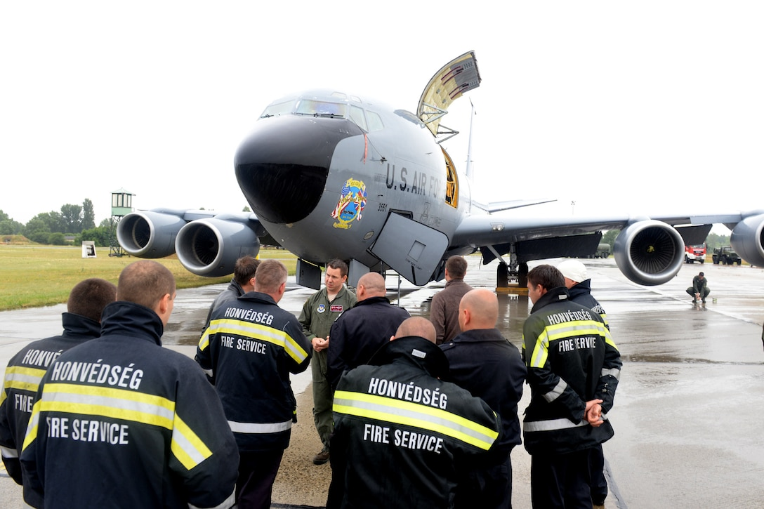 U.S. Air Force Maj. Benjamin Kline, center, 100th Air Refueling Wing KC-135 Stratotanker pilot and command post chief from Taylor, Mich., briefs Hungarian air force firefighters on the aircraft's safety procedures June 24, 2015, during air refueling familiarization training on Kecskemét air base, Hungary. Hungarian, U.S. and Swedish air force personnel met for a two-week familiarization period enabling the Hungarian JAS-39 Gripen pilots to successfully perform air refueling for the first time. (U.S. Air Force photo by Senior Airman Kate Thornton/Released)