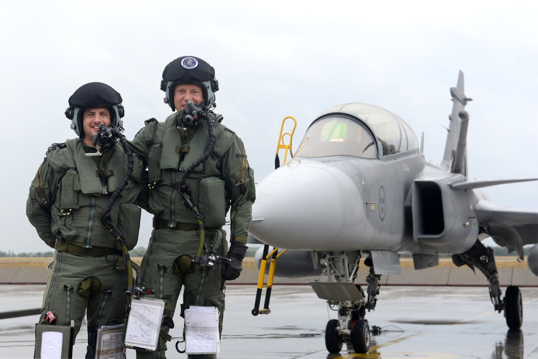 A Hungarian air force JAS-39 Gripen pilot, left, and Swedish air force Capt. Fredrik Borgsrtöm, Swedish AF Gripen Operational Testing and Evaluation instructor pilot, pose for a photo after completing the first air refueling training sortie in Hungarian history June 24, 2015, during air refueling familiarization training on Kecskemét air base, Hungary. Hungarian, U.S. and Swedish air force personnel met for a two-week familiarization period enabling the Hungarian JAS-39 Gripen pilots to successfully perform air refueling for the first time. (U.S. Air Force photo by Senior Airman Kate Thornton/Released)