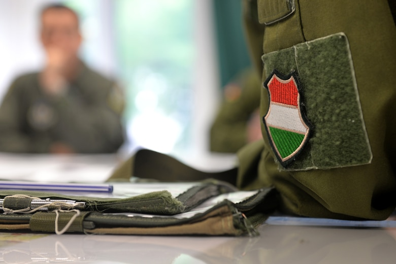 A Hungarian air force JAS-39 Gripen pilot listens to a pre-flight brief prior to flying June 24, 2015, during air refueling familiarization training on Kecskemét air base, Hungary. Hungarian, U.S. and Swedish air force personnel met for a two-week familiarization period enabling the Hungarian JAS-39 Gripen pilots to successfully perform air refueling for the first time. (U.S. Air Force photo by Senior Airman Kate Thornton/Released)