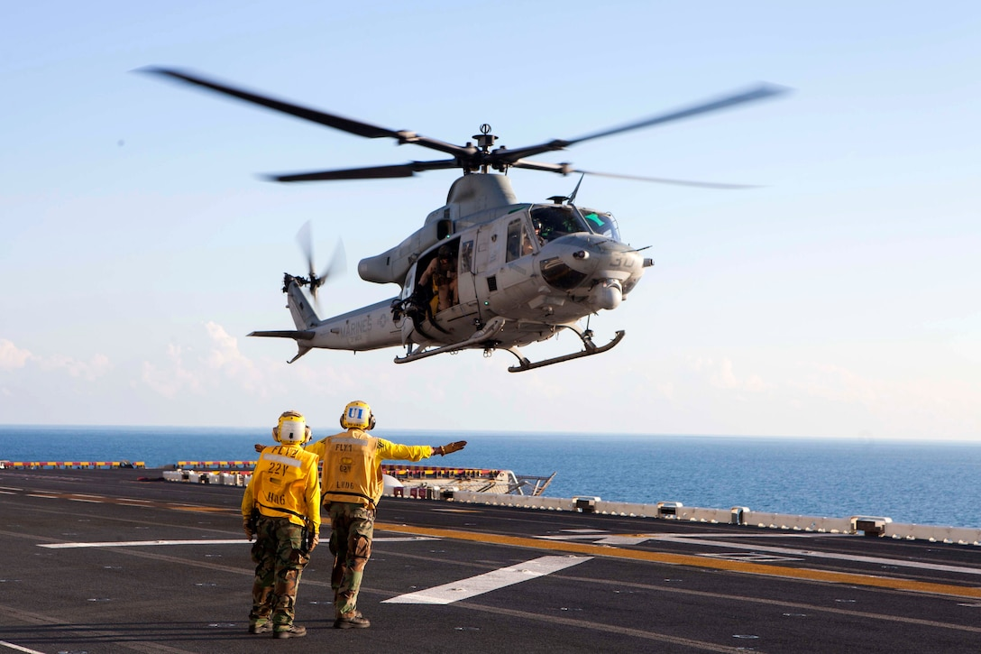 U.S. sailors give landing signals to a UH-1 Huey helicopter during exercise Talisman Sabre 2015 aboard the USS Bonhomme Richard at sea near Australia, July 11, 2015. The sailors are boatswain's mates.