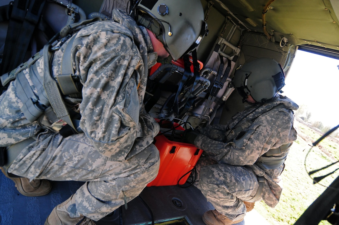 U.S. Army Reserve Spc. Matthew Lance and Sgt. James Hanson, crew chiefs with A Company, 2-238th Aviation Regiment, 11th Aviation Command, prepare a UH-60L Black Hawk helicopter to be used for water bucket training in Hemet, Calif., Feb. 10, 2015. This training was conducted to give the unit the ability to provide Cal Fire support in fighting California wildfires. Training included: Water bucket training using Bambi Bucket's equipped with Torrentula valves, water drops, flight operations, sand tables, fire shelters and classroom training. (U.S. Army photo by Spc. Heather Doppke/released)