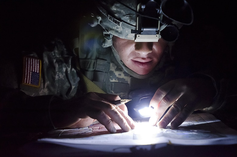 Spc. Randall Reinink, a parachute rigger representing the 143rd Sustainment Command (Expeditionary), plots points by flashlight during a night land navigation event during the 377th Theater Sustainment Command Best Warrior Competition at Fort Devens, Mass., April 14. Reinink, an Army Reservist and native of Fuquay-Varina, N.C., is among 10 Soldiers from across the 377th TSC vying for the command's Best Warrior title and the opportunity to represent the command at the U.S. Army Reserve Command competition at Fort Bragg, N.C., May 4-8, 2015. (U.S. Army photo by Spc. Tien Ngo)