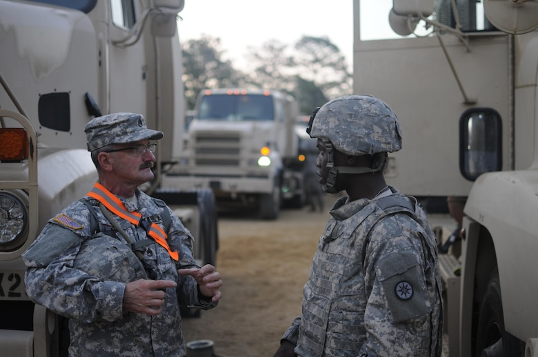 (Left) Staff Sgt. Dean Long and Pfc. Harvey Rohando, motor transport operators with the 630th Transportation Company, discus convoy safety standards prior to the departure of their petroleum supply convoy during a Quartermaster Liquid Logistics Exercise (QLLEX) at Fort Bragg, N.C., June. 12, 2015 QLLEX is an annual logistical movement event that will transport necessary petroleum and purified water throughout the U.S. (Sgt. Christopher Bigelow / Released)