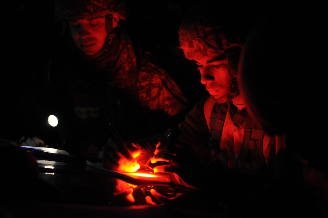 (Right) Spc. Brandon Perrodin, a quartermaster and chemical equipment repairer with the 14th Quartermaster Company, and (left) Pfc. Joshua St. Cyr, a dispatcher with the 915th Transportation Company, plot points on their maps during the nighttime land navigation course portion of the 316th ESC Best Warrior Competition. (Photo by Sgt. Christopher Bigelow / 316th ESC PAO)