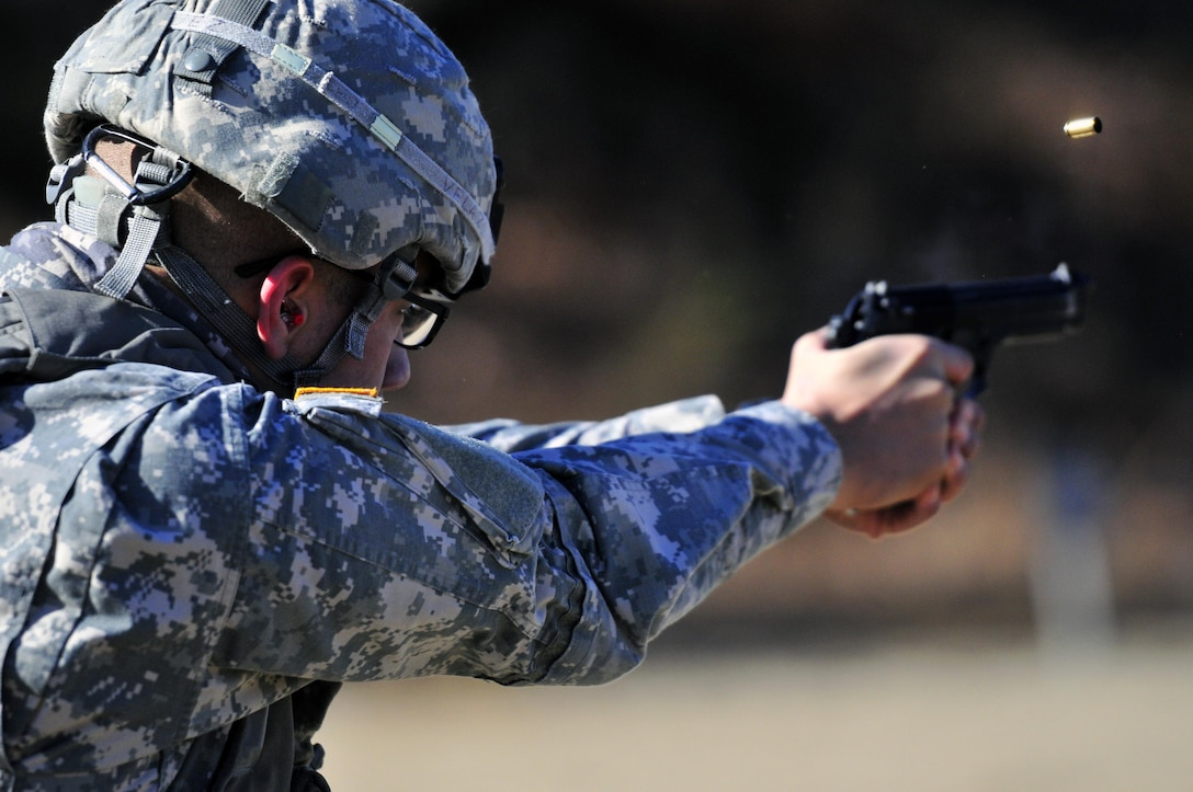 Spc. Michael Velazquez, an armament repairer representing the 237th Support Maintenance Company, fires an M9 pistol at the 316th Sustainment Command (Expeditionary) Best Warrior Competition qualification range. (Photo by Sgt. Christopher Bigelow / 316th ESC PAO)