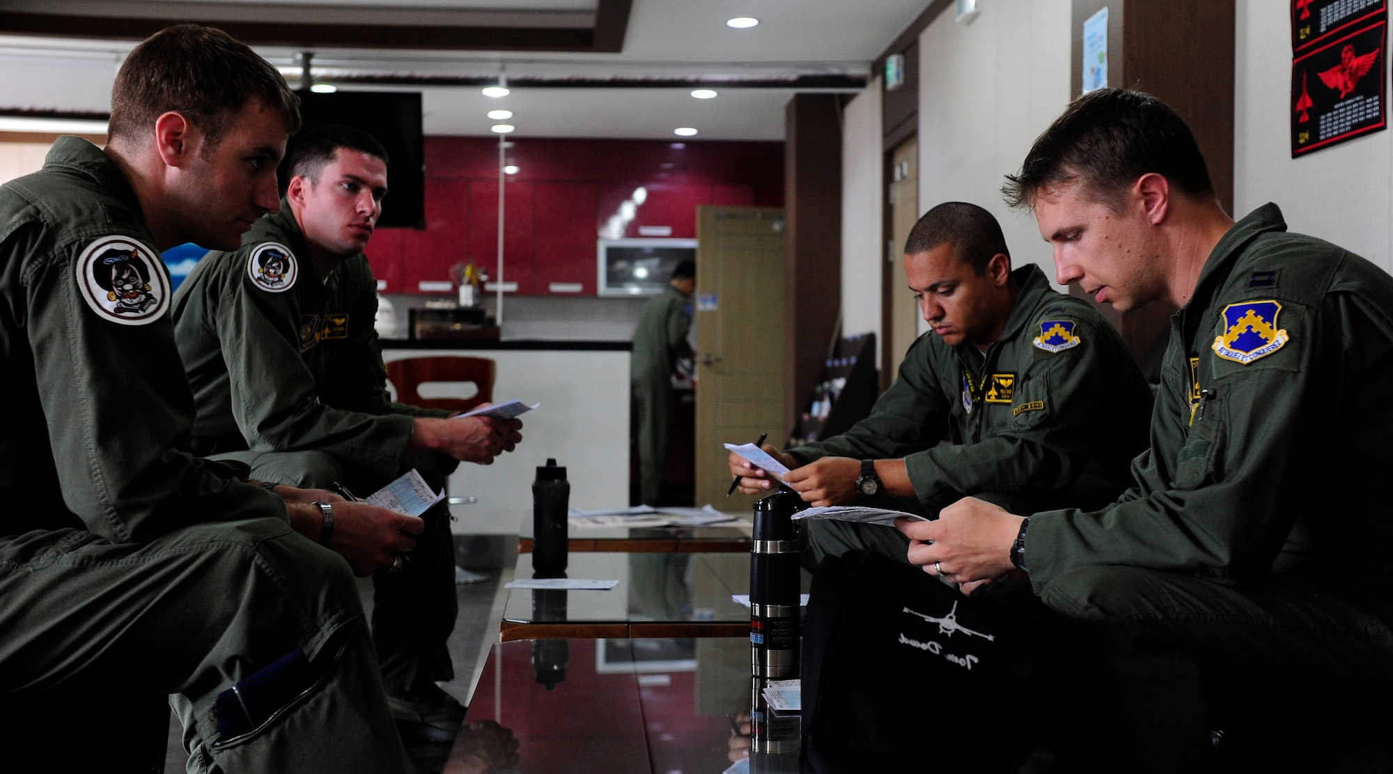 F-16 Fighting Falcon pilots from the 80th Fighter Squadron at Kunsan Air Base, South Korea, review and discuss flight procedures at Jungwon Air Base, South Korea, during Buddy Wing 15-6, July 9, 2015. Buddy Wing exercises are conducted multiple times throughout the year to sharpen interoperability between U.S. and South Korean forces so, if the need arises, they are always ready to fight as a combined force. (U.S. Air Force photo/Staff Sgt. Nick Wilson)