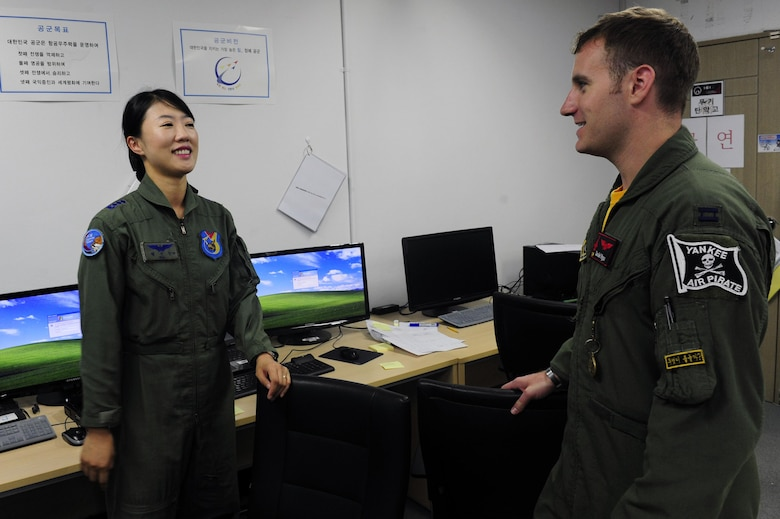South Korean air force Capt. Jin-Young Seol, a 19th Fighter Wing KF-16 Fighting Falcon pilot, talks to Capt. Daniel Wynn, the 80th Fighter Squadron assistant director of operations, at Jungwon Air Base, South Korea, during Buddy Wing 15-6, July 10, 2015. Buddy Wing exercises are conducted multiple times throughout the year to sharpen interoperability between U.S. and South Korean forces so, if the need arises, they are always ready to fight as a combined force. (U.S. Air Force photo/Staff Sgt. Nick Wilson)