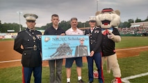 Joshua Laramie (second to the left) receives his Naval Reserve Officers' Training Corps scholarship worth $180,000 before an approximate crowd of 5,000 at Joseph L. Bruno Stadium in Troy, NY, Saturday, July 4th, 2015. Laramie is a sophomore enrolled in Ohio State University, native of Bethlehem, NY, and an aspiring Marine Corps F-35B Lightning II or AV-8B Harrier II pilot.