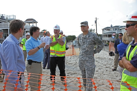 Col. William H. Graham, commander of the U.S. Army Corps of Engineers' North Atlantic Division, is briefed by USACE Philadelphia District Project Manager Keith Watson, during a tour of the Long Beach Island Storm Damage Reduction project on July 1, 2015. Work is designed to reduce future storm damages along the barrier island.