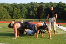 Staff Sgt. Alvaro Restrepo, canvassing recruiter with Recruiting Substation Northwest, supervises a fireteam conduct the four-man push-up station during a leadership seminar with the Vernon Township High School football team, July 13, 2015.