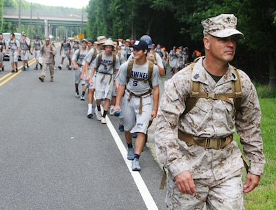 Sgt. Maj. Terry Harrelson, Recruiting Station New Jersey Sergeant Major, leads one of the sticks of Shawnee High School football players during the five-mile hike portion of a leadership seminar aboard Naval Weapons Station Earle in Colts Neck, N.J., July 1, 2015.