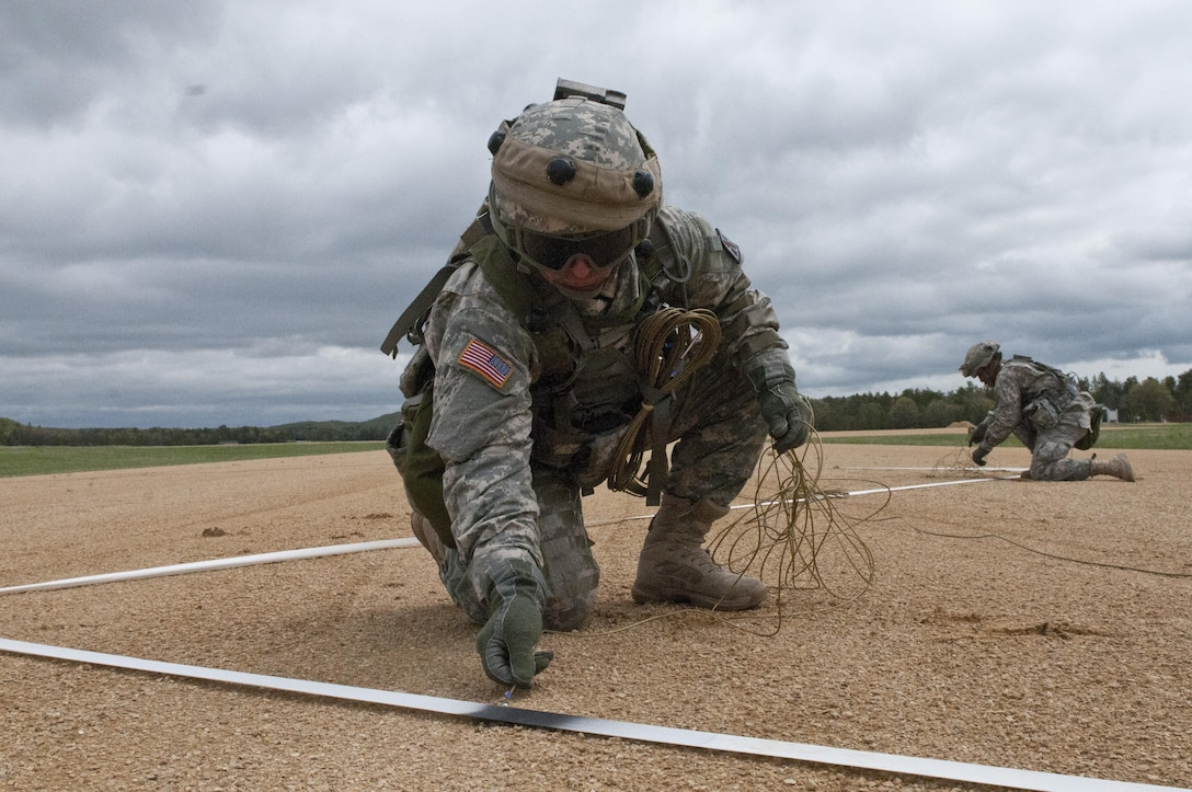 U.S. Army Reserve Spc. Nicholas Mixson, 344th Engineer Company, combat engineer, places a detonation cord during a situational training exercise lane to simulate destroying an airfield at Fort McCoy, Wis., May 12. The 344th Eng. Company participated in Warrior Exercise 86 15-02 May 2 to 22. (U.S. Army photo by Staff Sgt. Debralee Best)