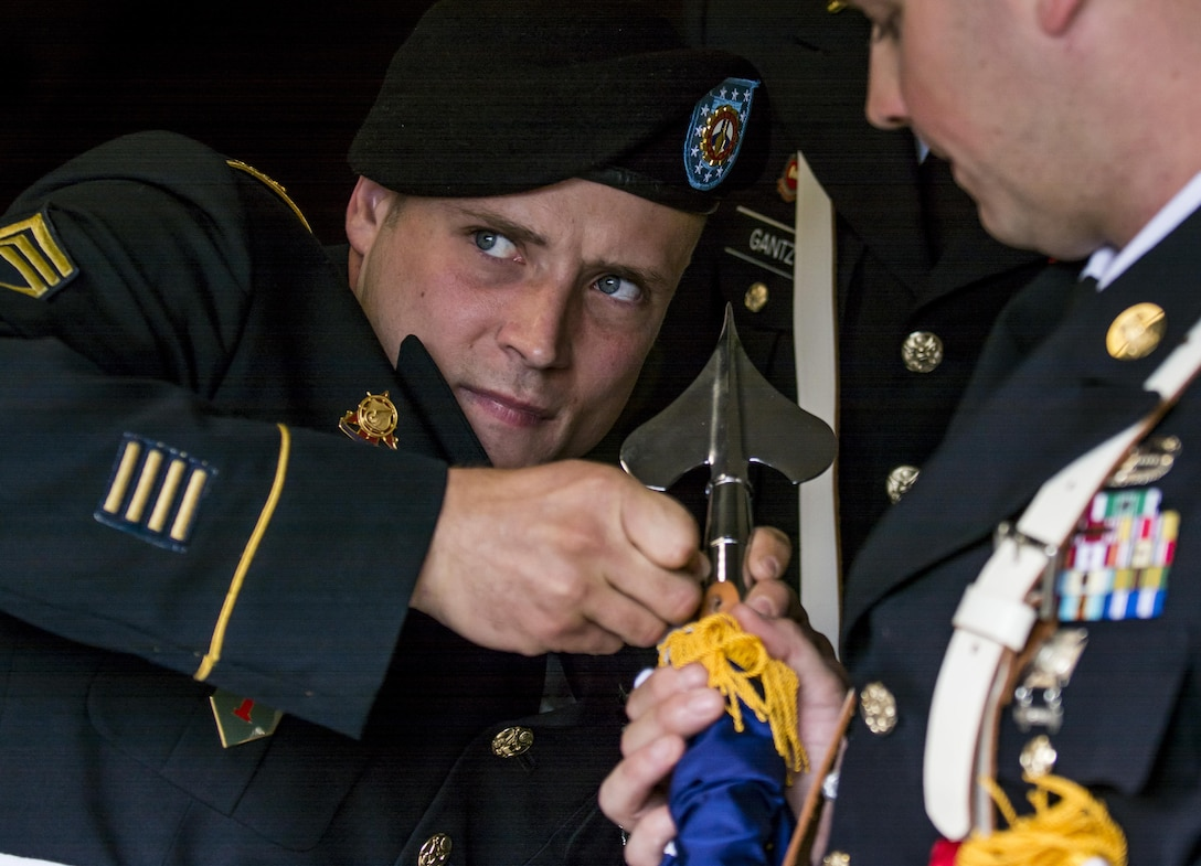Staff Sgt. John Pudowski, Army Reserve color guard team leader for the 416th Theater Engineer Command, fixes a screw on the the U.S. flag moments before having to go present at Wrigley Field for a Chicago Cubs game against the Los Angeles Dodgers, June 25. The 416th TEC is headquartered just 30 miles driving distance from Wrigley Field and is responsible for more than 12,000 Army Reserve Soldiers in 27 different states. The color guard team members were Staff Sgt. John Pudowski, Staff Sgt. Timothy Cooper, Sgt. Peter Garcia, Spc. William McGuigan and Spc. Travis Gantz. (U.S. Army photo by Master Sgt. Michel Sauret)