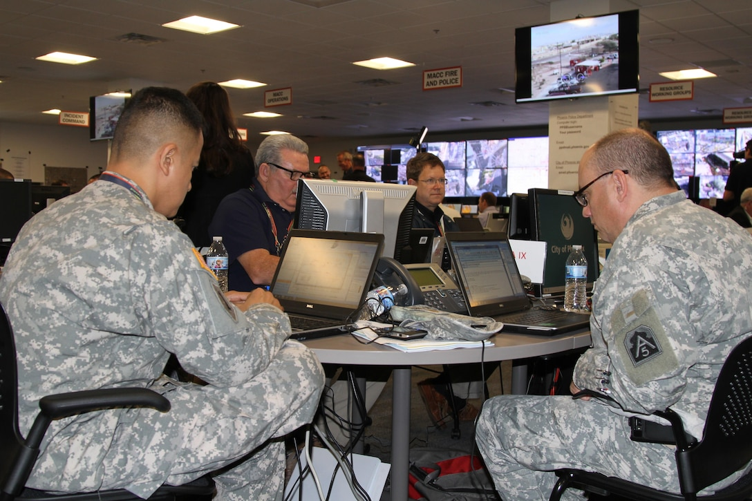 Soldiers from the Army Reserve Emergency Preparedness Liaison Officer work at their computers in the Multi Agency Coordination Center during the week prior to the Pro Bowl and Super Bowl, Jan. 27, 2015. The MACC was responsible for synchronizing and coordinating security efforts between state and federal agencies in the area leading up to Super Bowl XLIX. (U.S. Army photo by 1st Lt. Cavett Ishihara, 76th Operational Response Command)