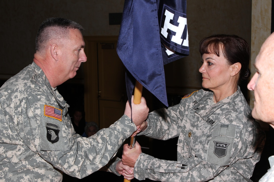First Sgt. Duane Hedrick, first sergeant of the 76th Operational Response Command Headquarters and Headquarters Company, passes the guidon to Maj. Sandra Peters, outgoing commander of the 76th ORC HHC, during the change of command ceremony held in Salt Lake City, March 15, 2015. During the ceremony, Peters relinquished command of the to Capt. Sunny Griffith, with friends and family in attendance. (U.S. Army photo by Staff Sgt. Kai L. Jensen, 76th Operational Response Command)