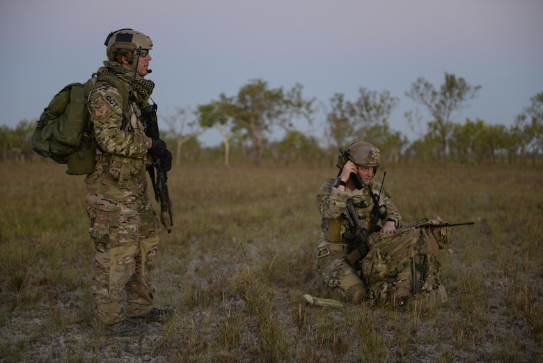 A special tactics combat controller and special tactics officer from the 320th Special Tactics Squadron get ready for a personnel recovery mission after performing a high altitude low opening jump during exercise Talisman Sabre in Northern Territory, Australia, July 10, 2015. The personnel recovery team consisted of four combat controllers, one special operations weatherman and one special tactics officer. (U.S. Air Force photo by Senior Airman Stephen G. Eigel)