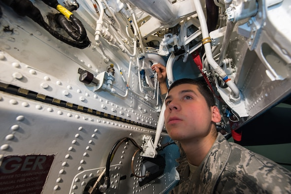 Airman 1st Class Saul Vasquez, 366th Equipment Maintenance Squadron phase inspection team member, poses for a photo inside the front wheel well of an F-15E Strike Eagle at Mountain Home Air Force Base, Idaho, June 25, 2015. The opening, barely larger than a foot wide, is laden with pipes and wires requiring absolute precision to maneuver. A simple misstep caused Vasquez to tear his radial artery on one of the many obstacles inside the belly of the aircraft. (U.S. Air Force photo by Airman 1st Class Connor J. Marth)