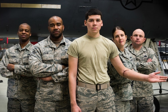 Airmen from the 366th Equipment Maintenance Squadron pose for a photo at Mountain Home Air Force Base, Idaho May 14, 2015. On April 2, Airman 1st Class Saul Vasquez (Center) tore his radial artery inside the belly of an F-15E Strike Eagle. Without the quick response and first aid training of squadron personnel, he may not be alive today. (U.S. Air Force photo by Airman Connor J. Marth)