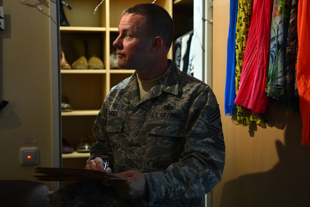U.S. Air Force Chief Master Sgt. Brian Gates, 52nd Fighter Wing command chief, looks over a dorm room during the Dorm of the Quarter competition at Spangdahlem Air Base, Germany, July 8, 2015. In addition to judging the common areas of each dorm, inspectors also looked over two dorm rooms, one chosen by dorm residents and one randomly chosen during the inspection. (U.S. Air Force photo by 2nd Lt Meredith Mulvihill/Released)