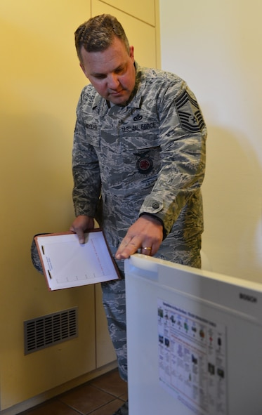 U.S. Air Force Chief Master Sgt. Timothy Randolph, installation fire chief, inspects the inside of a refrigerator as part of a walkthrough of Dorm 225 during the Dorm of the Quarter competition at Spangdahlem Air Base, Germany, July 8, 2015. The first round of the competition was graded by a panel of four judges, with the top three dorms making it through to the final round later in the day. (U.S. Air Force photo by 2nd Lt Meredith Mulvihill/Released)