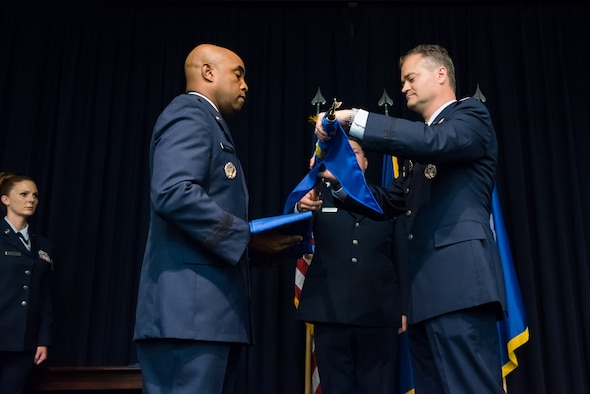 Brig. Gen. Trent Edwards, 37th Training Wing commander, Joint Base San Antonio-Lackland, Texas, prepares to sheath a guidon from Col. Steven Cabosky, Air Advisor Academy commandant, during an inactivation ceremony in the Air Advisor Academy at Joint Base McGuire-Dix-Lakehurst, N.J., July 10, 2015. The U.S. Air Force Expeditionary Center officially assumed the responsibility of being the Air Force's sole provider of training for general purpose force Air Advisors. (U.S. Air Force photo by Russ Meseroll/Released)