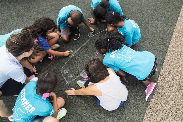 Liz Frost (left), Joint Base San Antonio-Randolph Youth Center assistant, helps a group of children start their own chalk drawing during an 'Image Makers' class July 8 at JBSA-Randolph. The class shows children how to both create a scene on the ground and have a partner capture them within the picture. (U.S. Air Force photo by Senior Airman Alexandria Slade/Released)