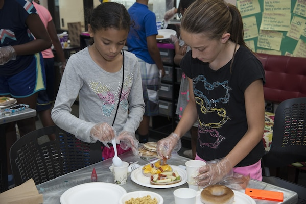 """Sofia Jackson  and Cheyenne Gramlick  prepare their dish, """"spicy-yummy-breakfast"""", for an """"Iron Chef"""" cooking contest July 9, 2015 at the Joint Base San Antonio-Randolph Youth Center. More than 500 children are involved in activities and programs provided by Randolph Youth Programs each year. (U.S. Air Force photo by Airman 1st Class Stormy Archer/Released)"""