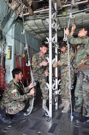 "Four Afghan National Army flight medics work as a team to reconfigure the cargo compartment of a C-130H Hercules from netted seating to metal stanchions that hold stretchers for a ""simulated"" medical evacuation, or medevac, flight at Hamid Karzai International Airport, July 9, 2015. The Train, Advise, Assist Command – Air (TAAC-Air) advisers provide weekly training to the ANA and Afghan air force to further develop and grow their fight medics. (U.S. Air Force photo/Capt. Eydie Sakura/released)"
