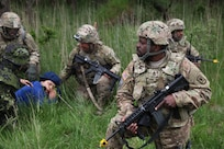 U.S. Army Sgt. 1st Class Jerome Smith, center, a civil affairs noncommissioned officer with Company B, 457th Civil Affairs Battalion, 361st Civil Affairs Brigade, 7th CSC and a native of Tampa, Fla., pulls security for a civilian role player with a simulated injury June 17, 2015, while U.S. Army Sgt. Jairo Navas, a civil affairs noncommissioned officer with Company B, 457th CA Bn., 361st CA Bde., 7th CSC and a native of New York, provides rear security and U.S. Army Staff Sgt. Mark Korte, center left, a civil affairs noncommissioned officer with Company B, 457th CA Bn., 361st CA Bde., 7th CSC and a native of El Cerrito, Calif., checks on her condition during the Danish Army's Civil Military Cooperation Support Team, 2nd Armored Infantry Battalion's NATO Response Force validation and training exercise Brave Lion 15, June 8-19, 2015. (Photo by Sgt. 1st Class Matthew Chlosta, 7th CSC Public Affairs Office)