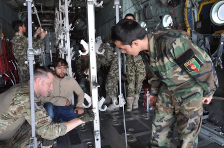 Master Sgt. Matthew Scott (left) points out to an Afghan National Army flight medic the importance of measurement and balance in the metal stanchions in the back of a C-130H Hercules at Hamid Karzai International Airport, Afghanistan, July 9, 2015. Scott is an aeromedical evacuation technician and emergency room manager at Eglin Air Force Base, Fla., who is currently the senior enlisted adviser at the nearby NATO clinic in Kabul. (U.S. Air Force photo/Capt. Eydie Sakura)