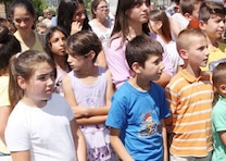 """Local children assemble during the dedication and ribbon-cutting ceremony June 11 for their school in Kucove, Albania. Nearly 600 students ages 6-15 attend the """"28 Nentori"""" facility, which was built in 1964 and had never been fully renovated."""