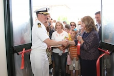 """Navy Cmdr. Ralph Shield, U.S. Embassy Tirana's defense attaché, shakes hands with school director Mjaftoni Dhimitri after the ribbon-cutting ceremony June 11 for """"28 Nentori,"""" a local nine-year school in Kucove, Albania."""