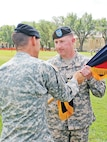 Brig. Gen. Eric Wesley, left, acting senior mission commander, 1st Inf. Div., passes the 1st ABCT colors to Col. Timothy Hayden, the new 1st ABCT, 1st Inf. Div., commander.