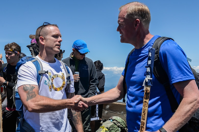 An Airman thanks Chief Master Sgt. of the Air Force James A. Cody for hiking alongside members from Yokota Air Base at Mount Fuji, Japan, July 11, 2015. Cody invited Yokota AB personnel to join him on the hike so that he could take time to interact with them. (U.S. Air Force photo/Airman 1st Class Elizabeth Baker)