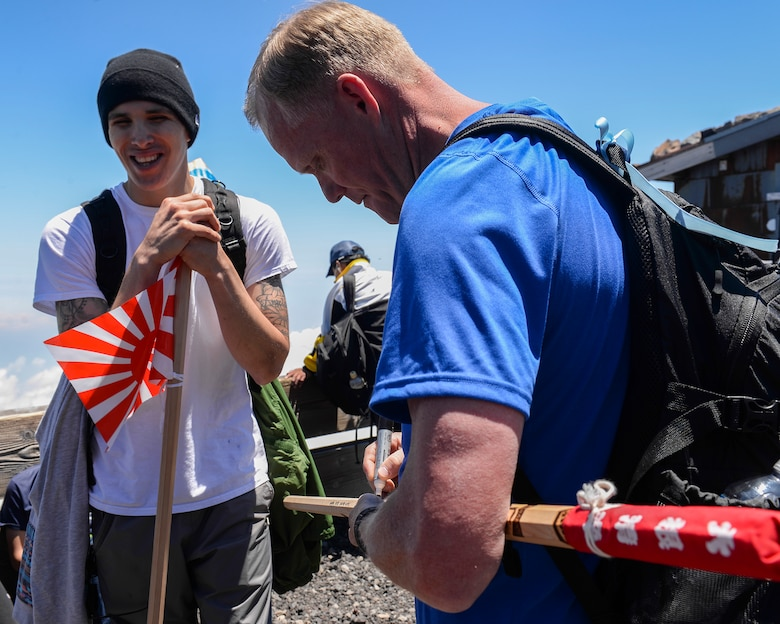 Chief Master Sgt. of the Air Force James A. Cody signs a walking stick for an Airman at the summit of Mount Fuji, Japan, July 11, 2015. During his trip to Japan, Cody extended an opportunity to 85 Yokota Air Base personnel to join him on a resiliency day trip to the summit of Mount Fuji. (U.S. Air Force photo/Airman 1st Class Elizabeth Baker)