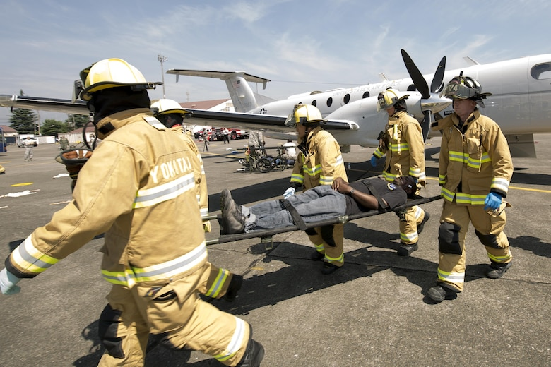 Yokota firefighters transport a simulated victim from an aircraft clash site during an Emergency Management Exercise at Yokota Air Base, Japan, July 13, 2015. Yokota conducted a Samurai Readiness Training Week to enhance readiness for real-world situations. (U.S. Air Force photo by Osakabe Yasuo/Released)