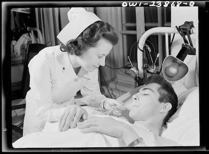 Army Nurse Lt. Frances Bullock cares for a Soldier encased in a body cast drink fruit juice from a straw in May 1943. During the World War II, there were more than 59,000 Army nurses on duty.