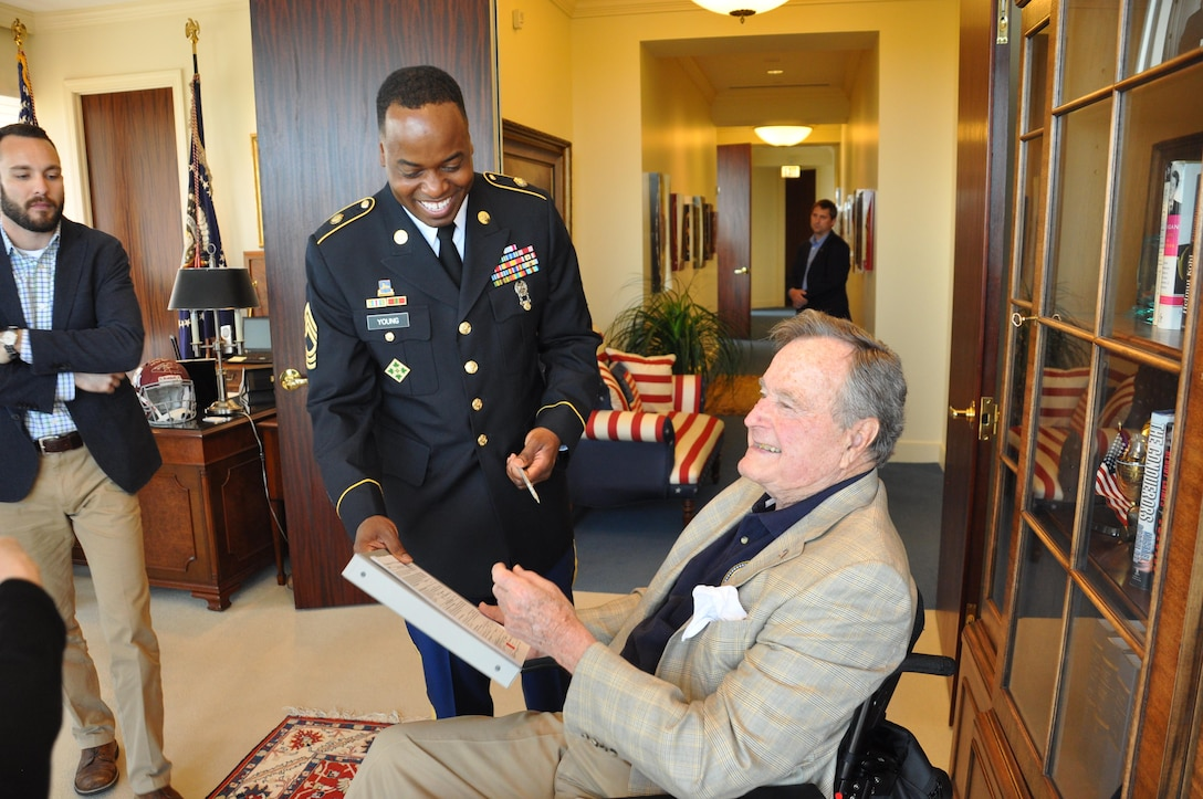 In this image released by the Army Reserve's Military Intelligence Readiness Command, former President George H.W. Bush (right) and Master Sgt. Branden Young (left) share a moment after Bush signed as the witness to Young's military re-enlistment contract during a ceremony in Houston, Texas, Friday, April 25, 2014. Young, a Virginia-based reservist, successfully requested Bush as the official to preside over the ceremony and sign the required documents. Young -- along with his family, friends and members of his unit -- traveled to Bush's post-presidential office in Houston for the event. Military units use formal re-enlistment ceremonies as a way to recognize ongoing service, as well as to encourage retention. (Photo/75th Training Command, Army Reserve Maj. Adam Collett)